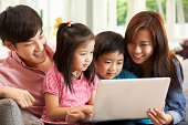 Chinese Family Using Laptop Whilst Relaxing On Sofa At Home