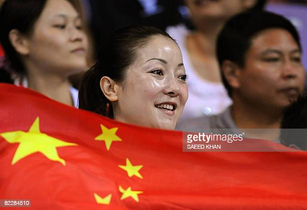 A Chinese fan waves her national flag to celebrate China victory over Angola after their 2008 Olympics Games women's handball match on August 13 2008...