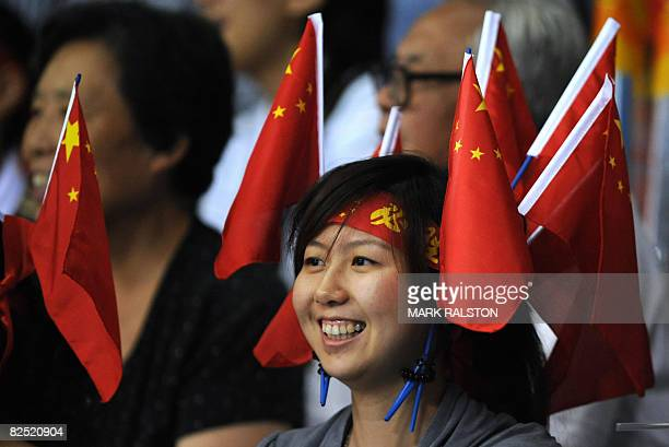 A Chinese fan wearing multiple flags in her hair watches the Cuba versus China women's volleyball bronze medal match in the 2008 Beijing Olympic...