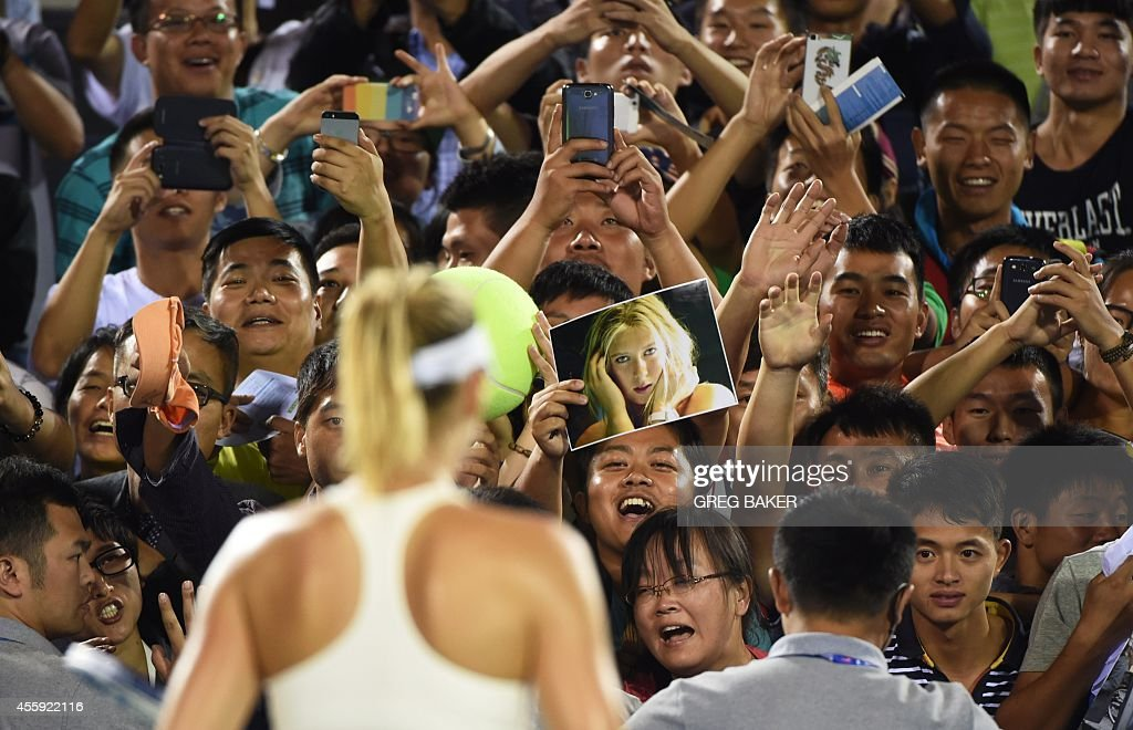 Chinese fans cheer Russia's Maria Sharapova after she defeated compatriot Svetlana Kuznetsova at the Wuhan Open tennis tournament in Wuhan in China's...