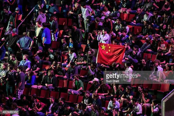 Chinese fans hold up their national flag after their team Vici Gaming wins over Evil Geniuses at The International DOTA 2 Championships on July 20...