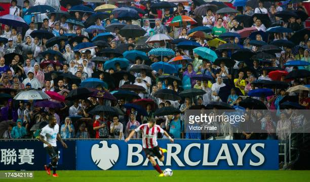 Chinese fans shelter under umbrellas during the Barclays Asia Trophy Semi Final match between Tottenham Hotspur and Sunderland at Hong Kong Stadium...