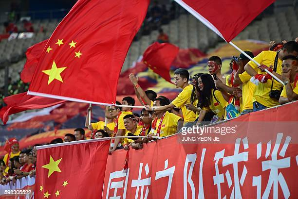 Chinese fans wave national flags during the 2018 World Cup qualifying football match between South Korea and China in Seoul on September 1 2016 / AFP...
