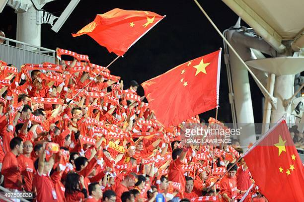 Chinese fans wave the national flag during a world cup qualifier at Mong Kok stadium in Hong Kong on November 17 2015 Hong Kong fans booed the anthem...