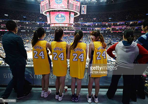 Chinese fans wear Kobe Bryant jerseys as they watch the LA Lakers' and Golden State Warriors' basketball match during the NBA Global Game 2013 tour...