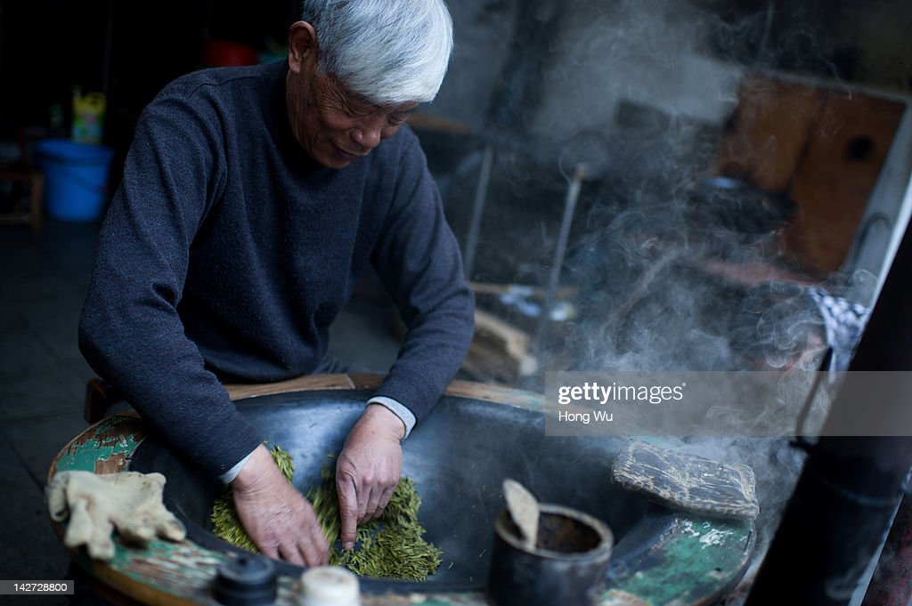 A Chinese farmer fries fresh Longjingtea leaves using traditional technics by hands at Meijiawu Village on March 29, 2012 in Hangzhou, China. Longjing is a green-tea, often called Dragon Well tea. The tea is typically picked by hand, and is of a high quality, earning the title of China Famous Tea. The Longjing tea begins to pluck before Chinese traditional Qingming Festival, the 15th day from the Spring Equinox or usually occurring around April 5. Many Chinese migrant workers from Jiangsu, Anhui, Jiangxi and other neighboring provices have been employed with 80 RMB yuan(US$12.68) to 120 RMB yuan(US$ 19.03) per day to pluck fresh Longjing tea leaves for villagers in many Longjing tea production villages in the outskirts of Hangzhou. The price of Longjing tea rose in recent years which aims to become to luxury goods. A high-end Longjing tea in Hangzhou sold for 50,000 RMB yuan(US$ 7930) half a kilo in 2012, the price rose 70 times in the last 12 years.