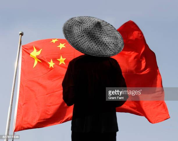 Chinese farmer standing near flag.