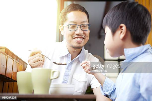 Chinese father and young son having breakfast on the balcony in the sunshine together