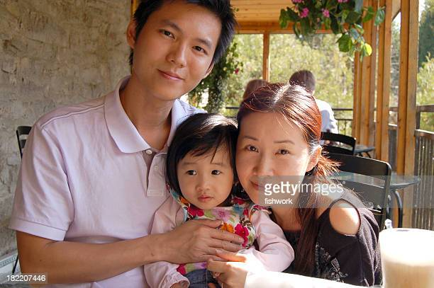 A Chinese father, mother, and baby at an outdoor table