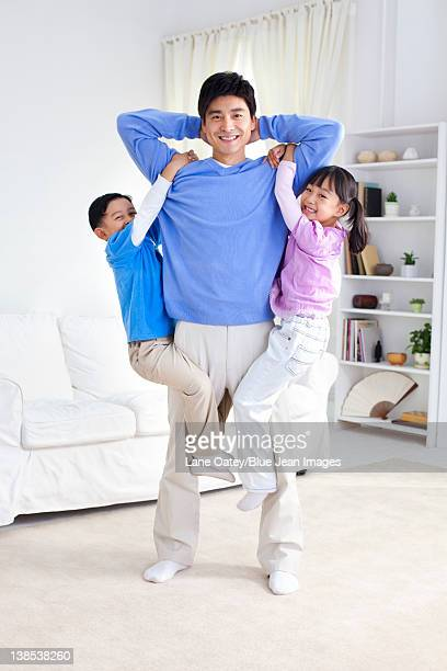 Chinese father with children hanging from his arms