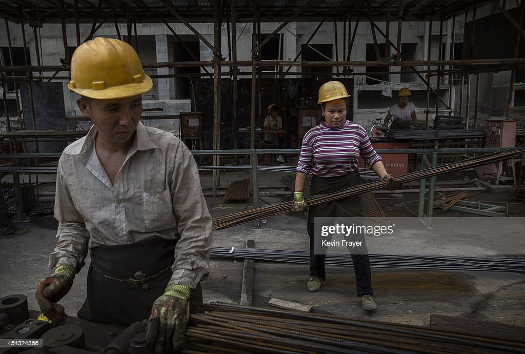 A Chinese female construction worker and a male colleague work at the building site of a new apartment complex on August 29, 2014 in Beijing, China. Rapid construction and widespread over-investment in Chinese property created a bubble that continues to deflate. Prices are down, the economy has cooled and newly-constructed projects in many parts of the country remain unoccupied. The housing market accounts for more than 15% of China's annual economic output and so the softening of the market is having a broader economic impact. Analysts believe that a property collapse is unlikely though as local governments are shoring up the sector.