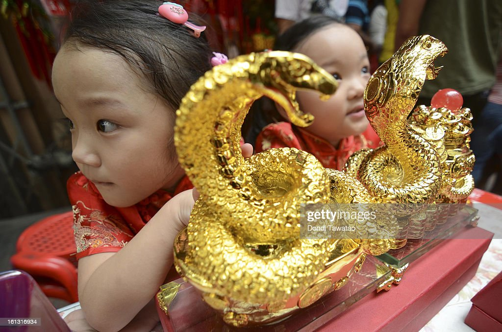Chinese Filipino children sit beside snake figurines being sold during the celebration of the Chinese New Year in the district of Binondo on February 10, 2013 in Manila, Philippines. The Chinese New Year (the year of the snake) has begun, known by locals as 'Spring Festival' or 'Lunar New Year'and is being celebrated annually by Chinese Filipinos who make up roughly 20 percent of the local population.