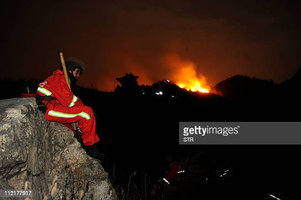 A Chinese firefighter takes a break while battling to extinguish a forest blaze in a remote mountainous region of Qinhuangdao northeast China's Hebei...