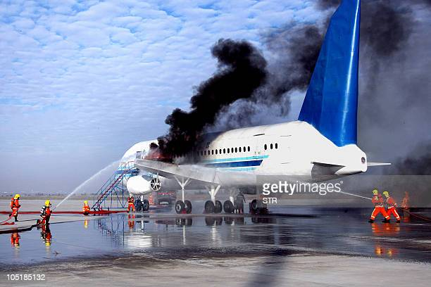 Chinese firefighters battle a burning aircraft during a drill at the Urumqi airport in far west China's Xinjiang region on October 10 2010 China has...