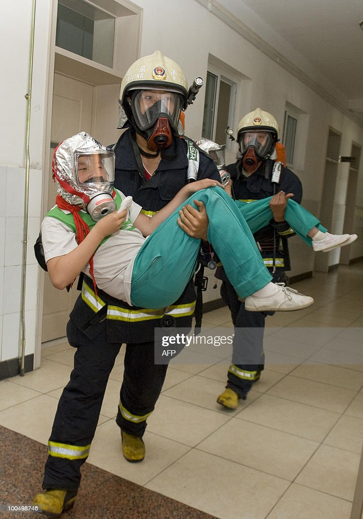 A Chinese fireman evacuates a student during a safety demonstration at an elementary school in Beijing on May 24, 2010. Beijing police are recruiting parents to join patrols of school grounds as cities nationwide beef up security following a spate of attacks on children. CHINA