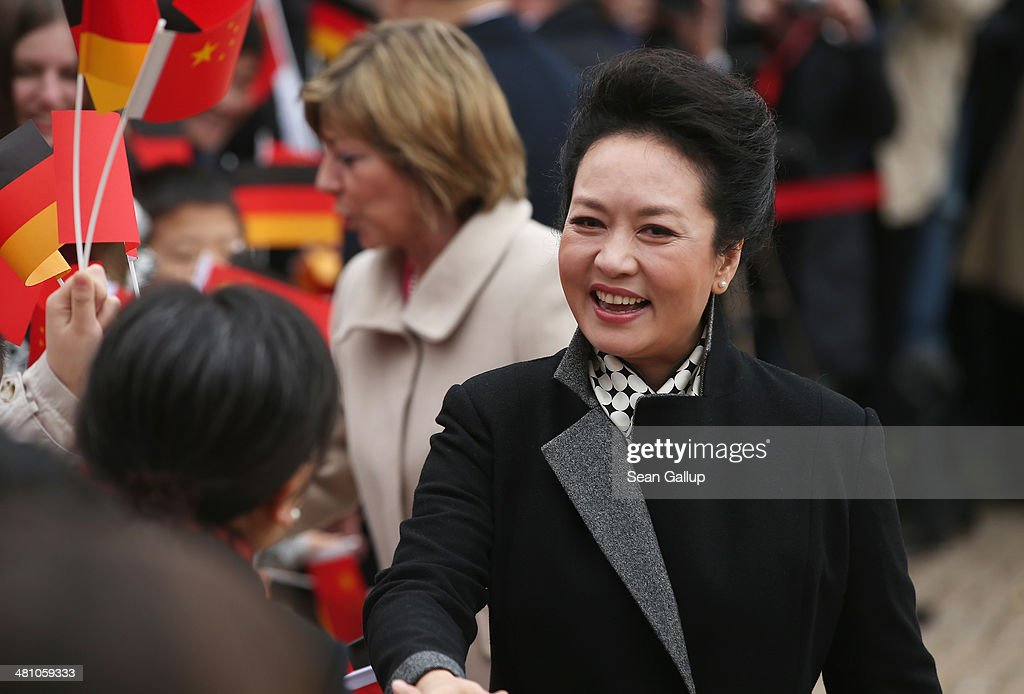 Chinese First Lady <a gi-track='captionPersonalityLinkClicked' href=/galleries/search?phrase=Peng+Liyuan&family=editorial&specificpeople=4379390 ng-click='$event.stopPropagation()'>Peng Liyuan</a> (R) and German First Lady <a gi-track='captionPersonalityLinkClicked' href=/galleries/search?phrase=Daniela+Schadt&family=editorial&specificpeople=7055235 ng-click='$event.stopPropagation()'>Daniela Schadt</a> (C) greet students at Schloss Bellevue on March 28, 2014 in Berlin, Germany. Chinese President Xi Jinping and First Lady <a gi-track='captionPersonalityLinkClicked' href=/galleries/search?phrase=Peng+Liyuan&family=editorial&specificpeople=4379390 ng-click='$event.stopPropagation()'>Peng Liyuan</a> are on a two-day official visit to Germany.