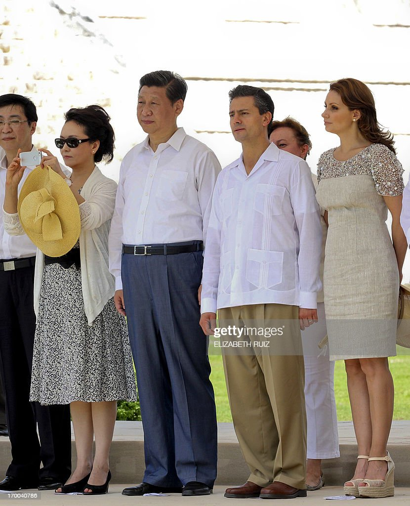 Chinese first lady Peng Liyuan (L) takes a picture as her husband China's President Xi Jinping (C) and Mexico's President Enrique Pena Nieto (2nd R) and his wife Angelica Rivera (R) pose during a visit at the archaeological site of Chichen itza, State of Yucatan, on June 6, 2013. Chinese President Xi Jinping on Tuesday kicked off a three-day visit to Mexico, which is seeking to narrow a huge trade gap with Beijing and attract investment from the world's number two economy. AFP PHOTO/Elizabeth Ruiz