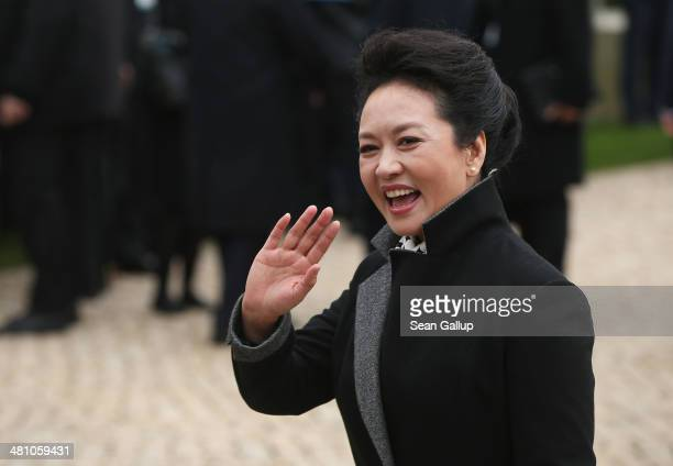 Chinese First Lady Peng Liyuan waves to students at Schloss Bellevue on March 28 2014 in Berlin Germany Chinese President Xi Jinping and First Lady...
