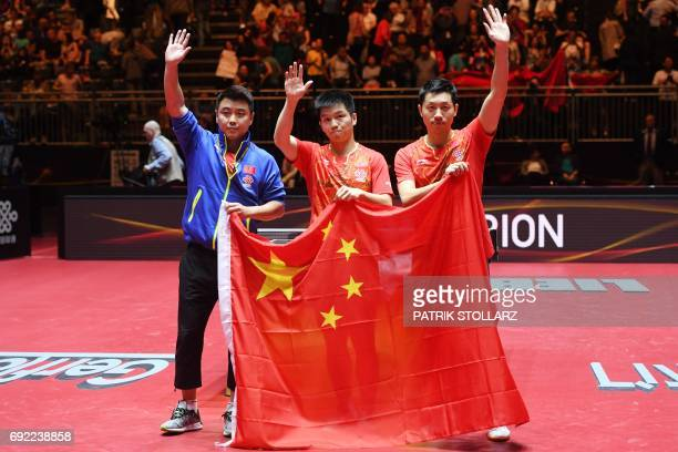 Chinese first placed men´s doubles Xu Xin and Fan Zhendong pose with teir coach Wang Hao and a Chinese flag after winning the final against Japanese...