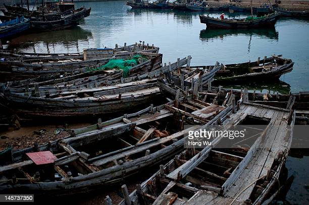 Chinese fisherman drives his fishing boat passing by many discarded fishing boats at a port on May 26 2012 in Qingdao China Marine fishery resources...