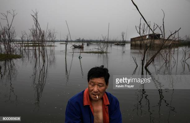 Chinese fisherman Li Guishu whose family home background was flooded out a decade ago sits in his boat near the site of a large floating solar farm...