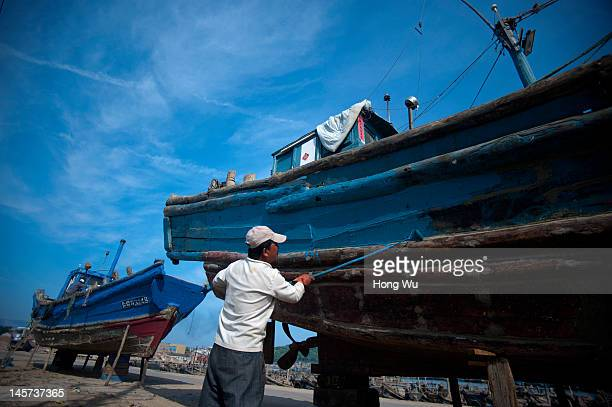 Chinese fisherman paints his fishing boat at a port on May 23 2012 in Qingdao China Marine fishery resources in China becomes less and lees due to...