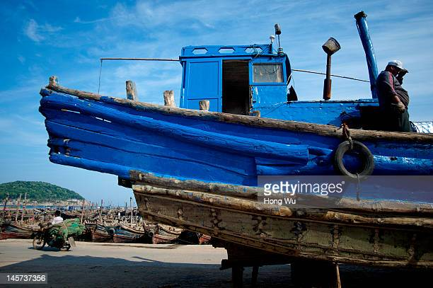 Chinese fisherman repairs his fishing boat at a port on May 23 2012 in Qingdao China Marine fishery resources in China becomes less and lees due to...