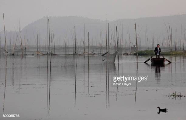 Chinese fisherman rides in a boat on land was flooded out more than a decade ago near the site of a large floating solar farm project under...