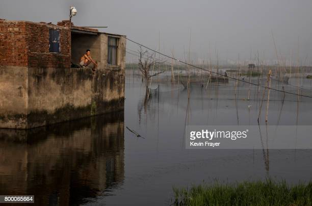 Chinese fisherman sits at his home that was flooded out more than a decade ago near the site of a large floating solar farm project under...