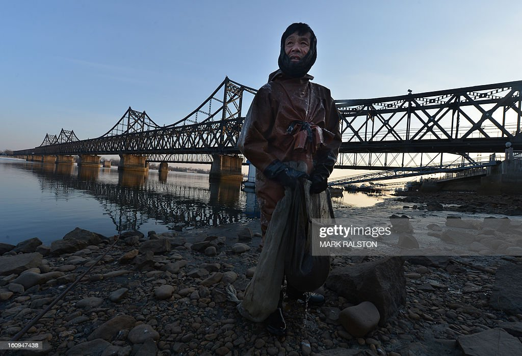A Chinese fisherman stands on the Yalu River beside the Sino-Korean Friendship bridge which leads to the North Korean town of Sinuiju on February 8, 2013 which is close to the Chinese city of Dandong. US Secretary of State John Kerry warned that North Korea's expected nuclear tests only increase the risk of conflict and would do nothing to help the country's stricken people. The country has vowed to carry out a third nuclear test soon, and concerns have been raised over the type of fissile material used in the device. AFP PHOTO/Mark RALSTON