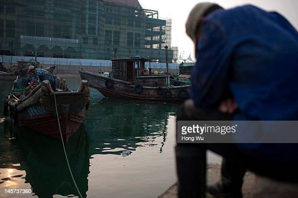 Chinese fisherman takes a nap at a port where building new commercial buildings on May 26 2012 in Qingdao China Marine fishery resources in China...