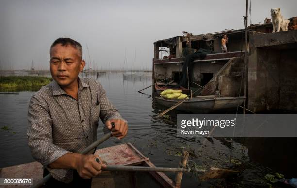 Chinese fisherman Wang Duoli whose family home background was flooded out more than a decade ago paddles in his boat near the site of a large...