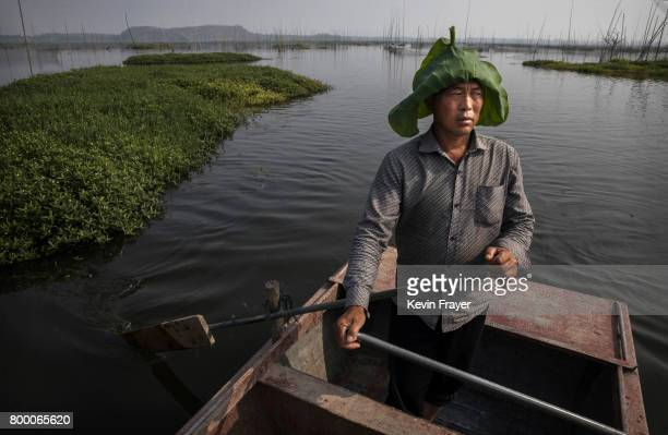 Chinese fisherman Wang Duoli whose family home was flooded out more than a decade ago paddles in his boat near the site of a large floating solar...