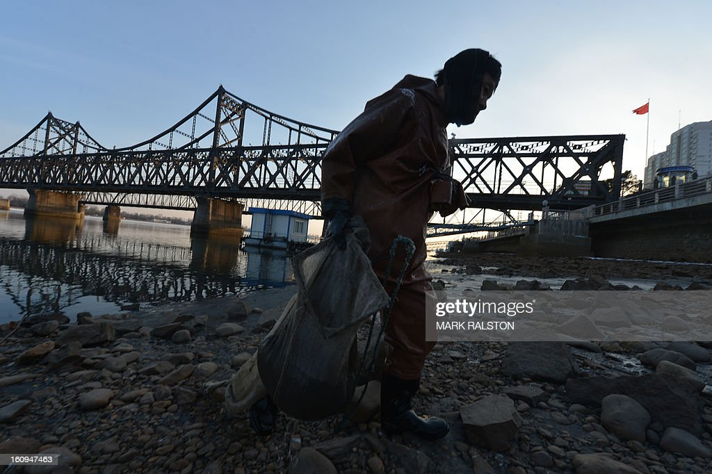 A Chinese fisherman works on the Yalu River beside the Sino-Korean Friendship bridge which leads to the North Korean town of Sinuiju on February 8, 2013 which is close to the Chinese city of Dandong. US Secretary of State John Kerry warned that North Korea's expected nuclear tests only increase the risk of conflict and would do nothing to help the country's stricken people. The country has vowed to carry out a third nuclear test soon, and concerns have been raised over the type of fissile material used in the device. AFP PHOTO/Mark RALSTON