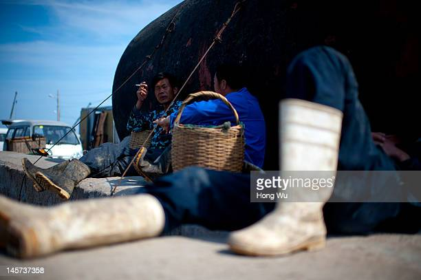Chinese fishermen rest at a port on May 23 2012 in Qingdao China Marine fishery resources in China becomes less and lees due to excessive fishing and...