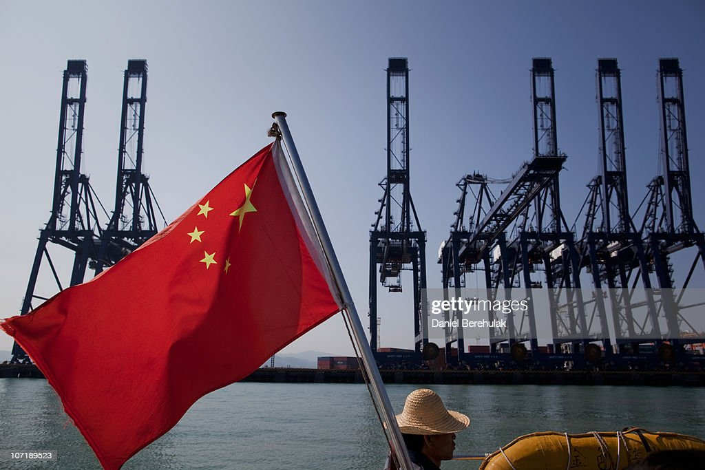 A Chinese flag attached to the back of a boat flaps in the wind as cargo containers sit on the dock of Shenzhen Port on November 28, 2010 in Shenzhen, China. According to the US Commercial Service, Shenzhen is one of the fastest growing cities in the world. Home of the Shenzhen Stock Exchange and the headquarters of numerous technology companies, the now bustling former fishing village is considered southern China's major financial centre.
