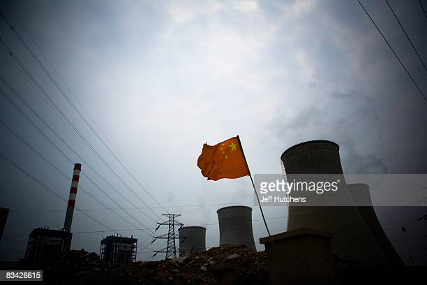 Chinese flag flies in front of a coal fired power plant rising across the skyline of rapidly China while fears of widespread industrial pollution...