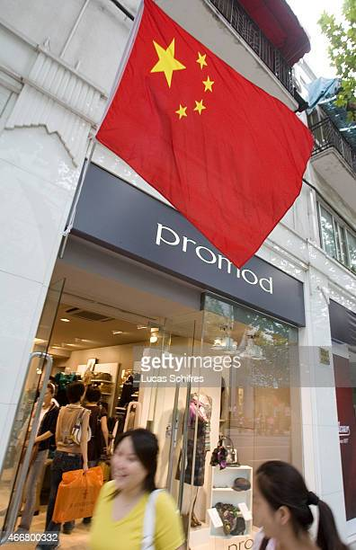 A Chinese flag is put up by a Promod clothing store for the upcoming celebration of China's National Day on famous commercial avenue Nanjing road on...