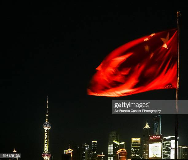 Chinese flag over Shanghai skyline at night