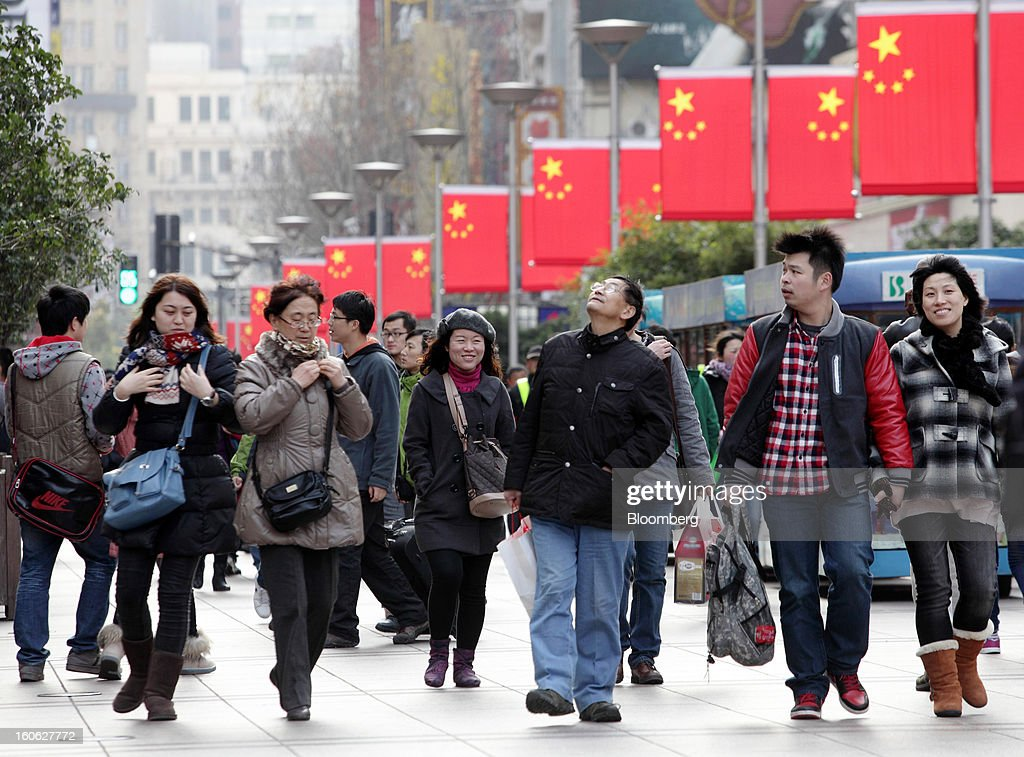 Chinese flags hang on lamp posts as pedestrians walk through the East Nanjing Road shopping area of Shanghai, China, on Friday, Feb. 1, 2013. China's services industries grew at the fastest pace since August as gains in retailing and construction aid government efforts to drive a recovery in the world's second-biggest economy. Photographer: Tomohiro Ohsumi/Bloomberg via Getty Images