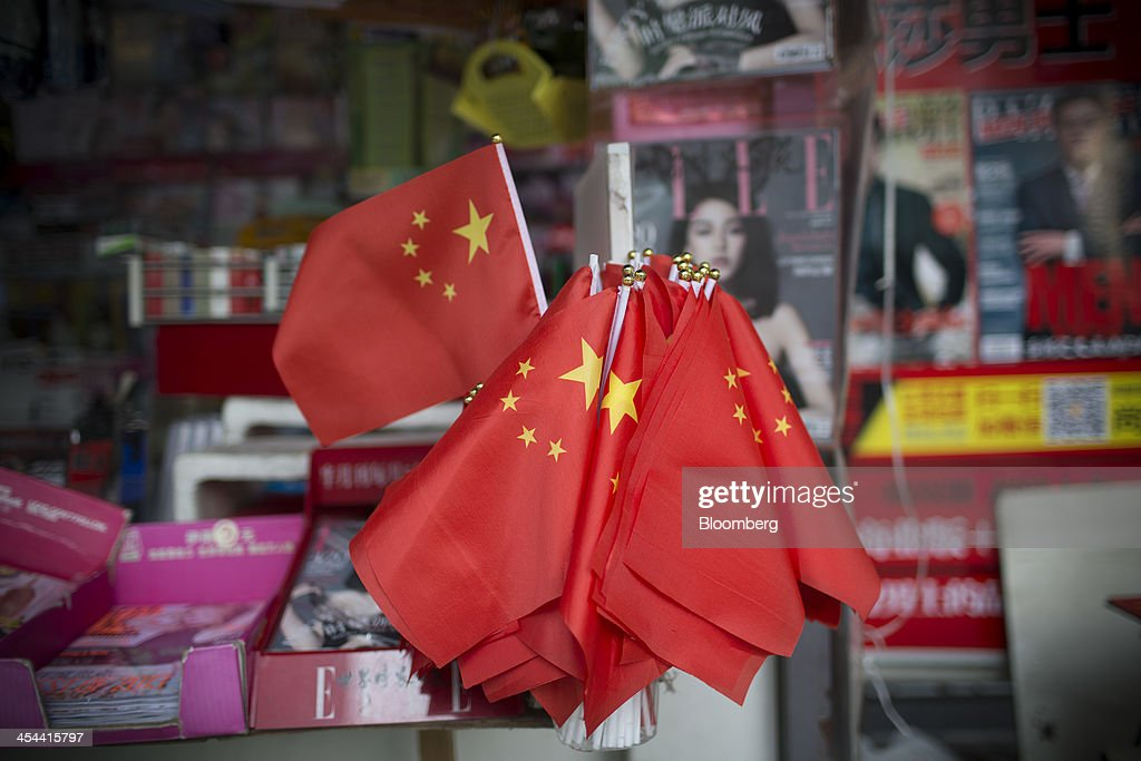 Chinese flags stand for sale at a magazine stall in the Tianhe district of Guangzhou, Guangdong province, China, on Saturday, Nov. 30, 2013. China's government may set its 2014 growth target at 7 percent, the Economic Information Daily reported on Dec. 3, citing the State Information Center. This compares with a goal of 7.5 percent for this year. Photographer: Brent Lewin/Bloomberg via Getty Images