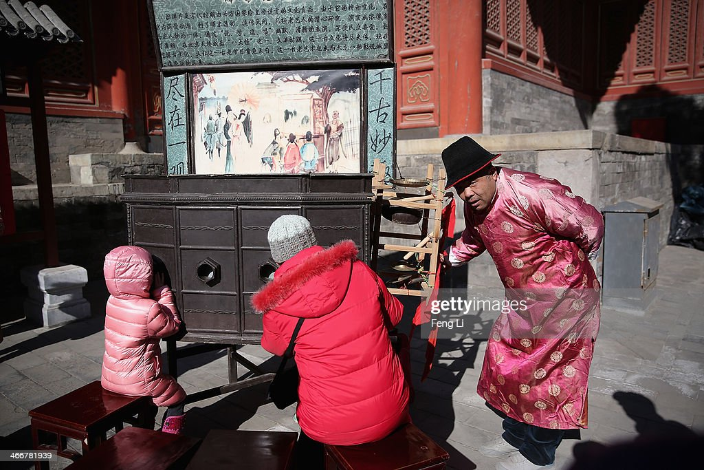 A Chinese folk artist (Right) perform traditional slide to two visitors during a Spring Festival temple fair on the fifth day of the Chinese Lunar New Year of Horse on February 4, 2014 in Beijing, China. The Chinese Lunar New Year of Horse also known as the Spring Festival, which is based on the Lunisolar Chinese calendar, is celebrated from the first day of the first month of the lunar year and ends with Lantern Festival on the Fifteenth day.