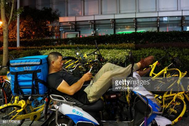 A Chinese food delivery man looks at his phone as he waits for orders in Shanghai on August 15 2017 The International Monetary Fund is scheduled to...