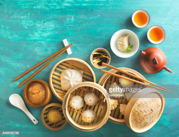 Chinese food dumpling and tea set on rustic table top.