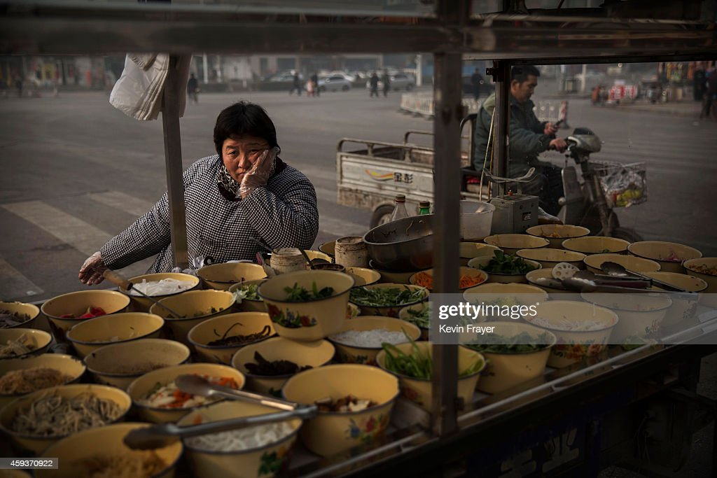 Chinese food vendor waits for customers at a market on November 21 2014 in Hebei just outside Beijing China China is challenged to ensure its food...