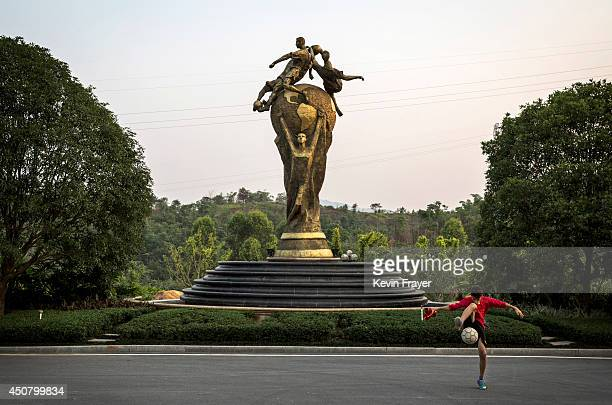 A Chinese football player plays with a ball next to a large likeness of the FIFA World Cup trophy as he waits for a ride after training at the...