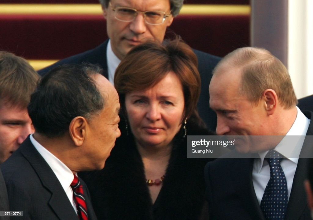Chinese Foreign Minister Li Zhaoxing (L) greets Russian President <a gi-track='captionPersonalityLinkClicked' href=/galleries/search?phrase=Vladimir+Putin&family=editorial&specificpeople=154896 ng-click='$event.stopPropagation()'>Vladimir Putin</a> (R) and his wife Ludmila (C) as they arrive at the Capital International Airport on March 21, 2006 in Beijing. Putin will discuss energy and military relations with China as well as Iran and North Korea issues during his two-day visit to Beijing.