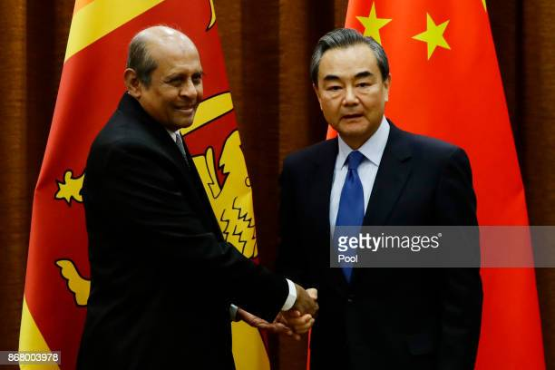 Chinese Foreign Minister Wang Yi and Sri Lanka's Foreign Minister Tilak Marapana shake hands before their meeting at the Ministry of Foreign Affairs...