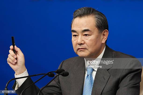 Chinese Foreign Minister Wang Yi answers questions during a news conference in the Media Center on March 8 2014 in Beijing China Yang said the put...