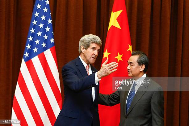 Chinese Foreign Minister Wang Yi greets visiting US Secretary of State John Kerry before their meeting at the Ministry of Foreign Affairs February 14...